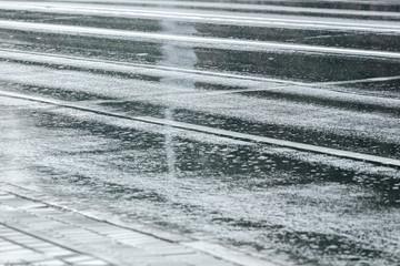 rain rippling on wet asphalt road. city street in autumn