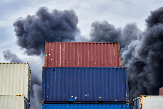 Shipping containers stacked in storage with plumes of black toxic smoke from a fire against a blue sky.
