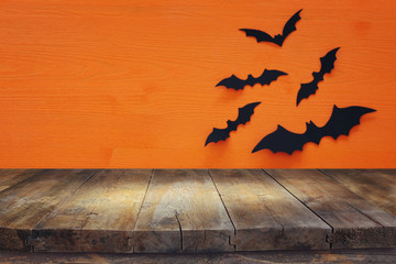 Halloween holiday concept. Empty rustic table in front of black bats background. Ready for product display montage.