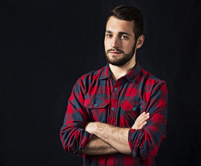 young guy in checkered shirt with a beard on a black background