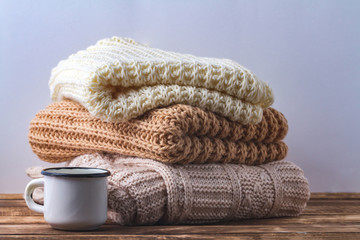 Winter, autumn clothes, knitted scarves and a white mug of hot cocoa on a white background.