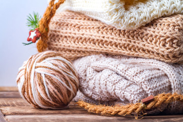 Warm, pastel clothes, knitted, pastel-colored scarves and a ball of knitting yarn on a white background. Winter, autumn clothes.