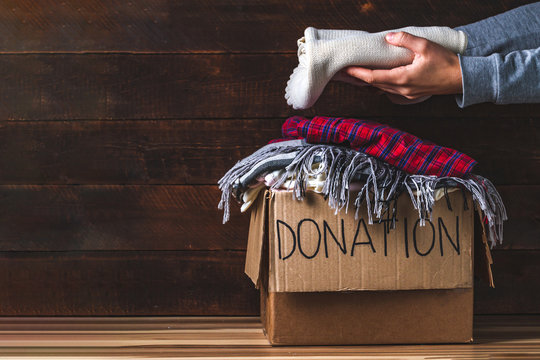 Donation concept. Donation box with donation clothes on a wooden background. Charity. Helping poor and needy people
