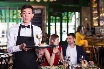 Man waiter is holding tray with wine and salad for clients