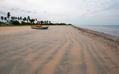Nivali beach with boat and streaky sand patterns in Trincomalee Sri Lanka Asia