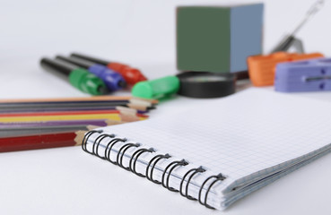 Notepad and blurred image of office supplies on white background