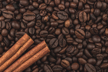 Roasted coffee beans and cinnamon sticks. Background, close-up view.