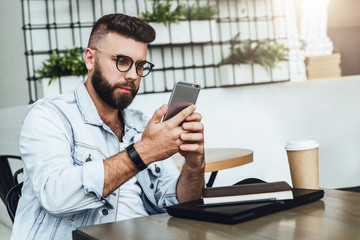 Bearded businessman sitting in cafe, talking on smart phone, working on laptop, freelancer working in coffee shop,