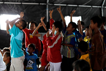 Children gather in a military tent to receive occupational therapy at a camp for displaced victims of the earthquake and tsunami in Palu