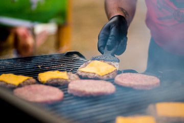 cook in gloves is cooking a cutlet with cheese for burgers on an open fire