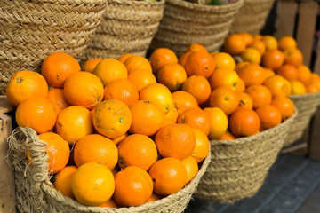 pile of juicy oranges in wicker baskets on market counter