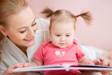 Mother and baby daughter reading book indoors