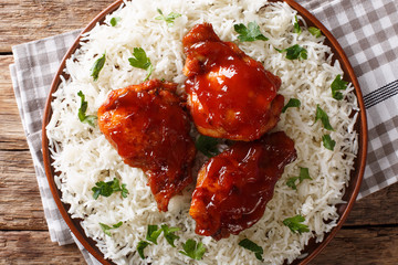 Delicious glazed chicken with spicy sauce and rice close-up on a plate on the table. horizontal top view from above
