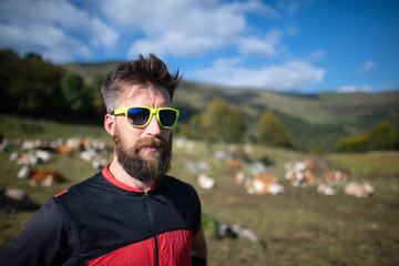 Sporty man with beard near a cows pasture