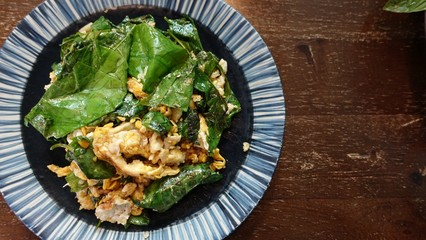 A white plate of delicious Stir-Fried Baegu Leaves or Gnetum gnemon or Melinjo with Eggs on banana leaf. Thai Southern traditional food style with Selective focus.