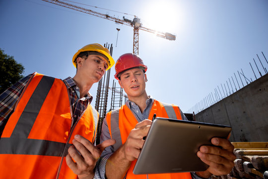 Architect  and structural engineer dressed in orange work vests and  helmets discuss a building project on the tablet on the open air building site with construction material