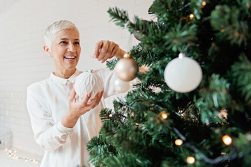 Beautiful woman decorating a Christmas tree