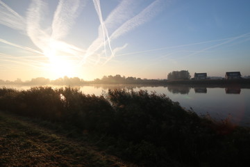 Sunrise with colored aircraft trails, fog on the meadows and dyke at River Hollandsche IJssel in the Netherlands at nieuwerkerk.