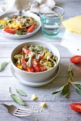 Pasta tagliatelle with fried sage and tomatoes. Top View Served Table