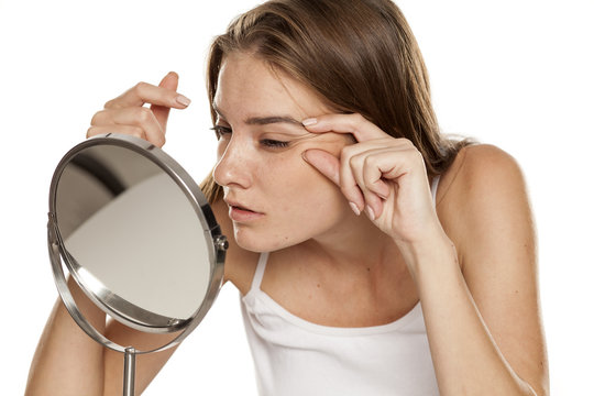 Young woman checking her wrinkles on her eyes
