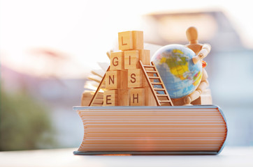 English wording on the thickness book with blurred world globe against the morning light