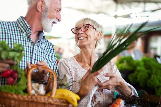 Smiling senior couple buying vegetables and at the merket