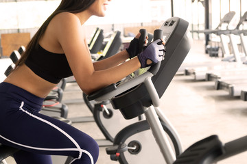 Sporty Woman Exercise bike cardio workout at fitness gym taking weight loss with machine aerobic.
