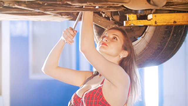 Sexy mechanic girl under the car with a spanner, looking up