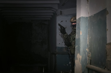 A army soldier takes aim with a pistol gun in his hands. Storming the building concept.