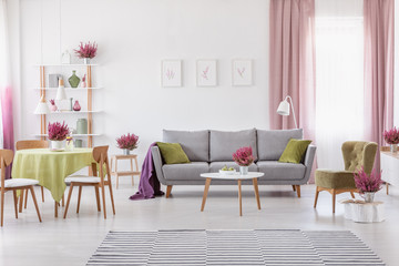 Elegant daily room with round table with wooden chairs and grey sofa with olive green pillows, stylish armchair next to it, real photo