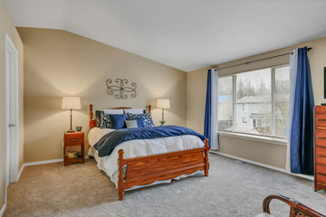 Master bedroom interior with warm yellow tones and blue curtains
