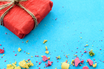 Blue background with gifts and crumbs of a multi-colored cake, top view