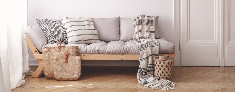 Panorama of pillows and blanket on wooden beige couch in white flat interior with door. Real photo