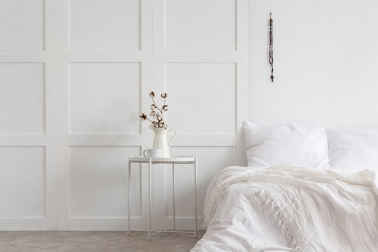 Flowers on table next to bed with pillows and sheets in white minimal bedroom interior. Real photo