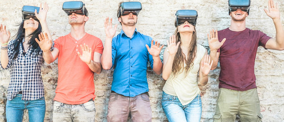 Young friends using virtual reality glasses outdoor