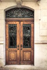 Vintage wooden door with metal lattice built in stone house