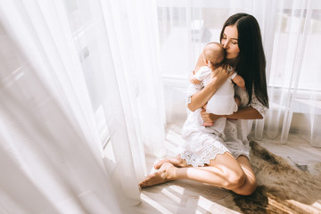 happy young mother kissing her baby while sitting on floor at home