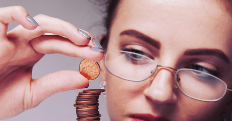 Beautiful business woman with column coins as symbol of investment or growth. (Money, wealth, entrepreneurship, discount, savings concept).