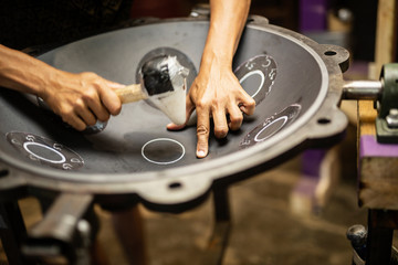 Hands designing handpan in a workshop