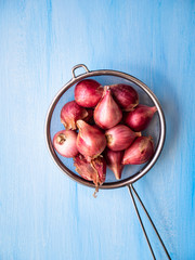 Shallots in the colander on a blue wooden background
