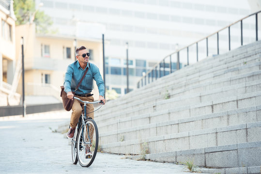 handsome middle aged businessman in sunglasses riding bike and looking away on street