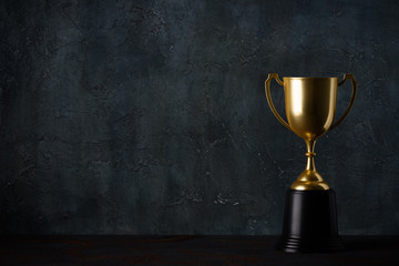 Golden trophy cup on table dark background with copy space