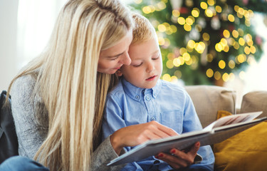 A mother and small boy sitting on a sofa at home at Christmas time, reading a book.