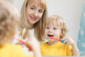 mother teaching kid teeth brushing in bathroom