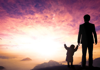 Father's Day concept: businessman father and child standing on the mountain top