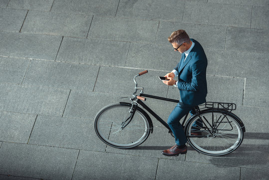 high angle view of businessman in formal wear using smartphone while standing with bicycle on street