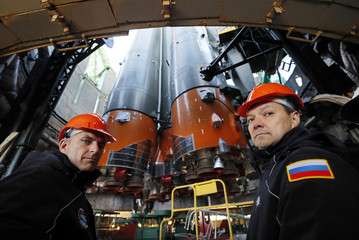Backup crew members Roscosmos cosmonaut Kononenko and CSA astronaut Saint Jacques look at the Soyuz booster rocket with the Soyuz MS-10 spacecraft installed on the launch pad at the Baikonur cosmodrome