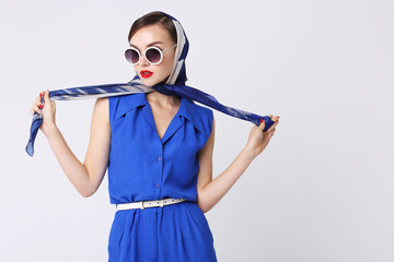 Young woman in retro style. Sunglasses and silk scarf, blue overalls.