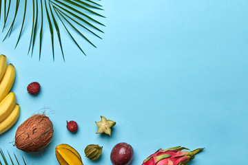 Corner frame of a green palm branch and a variety of tropical fruits on a blue background with space for text. Flat lay