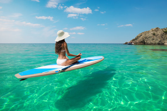 Young beautiful woman meditating in a sea at SUP paddleboarding. Healthy lifestyle. Girl in yoga pose relaxing in calm water.